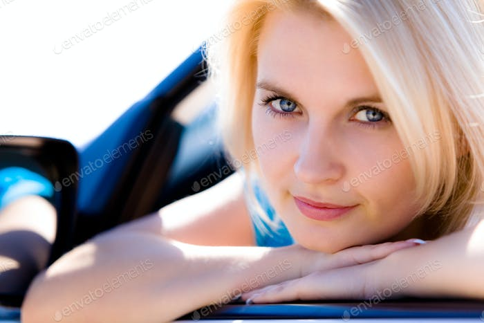 Positive cute young blue-eyed woman driver
