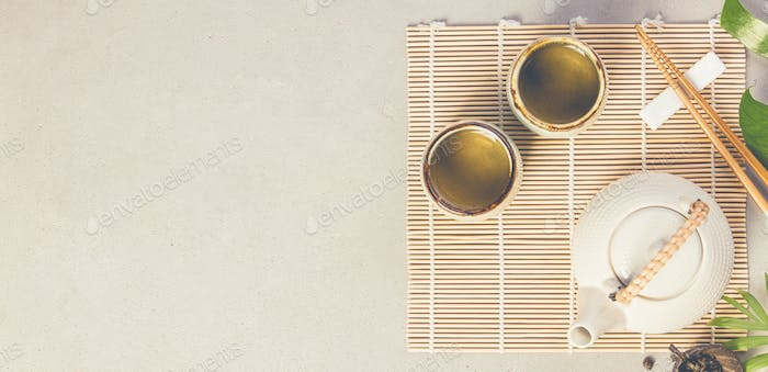 Asian food background - tea and chopsticks on a grey concrete background