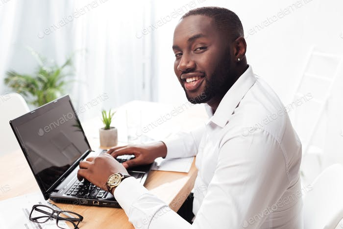 African American businessman happily looking in camera working on his laptop in office