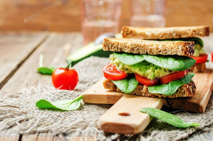 Smashed avocado spinach tomato grilled rye sandwich