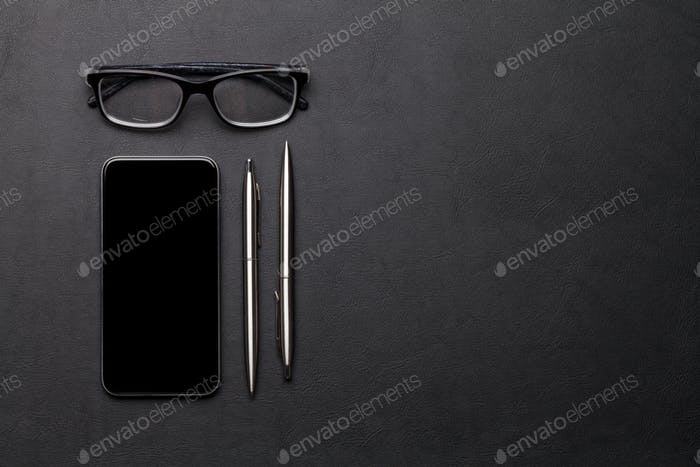 Office workplace table with smartphone, glasses and supplies