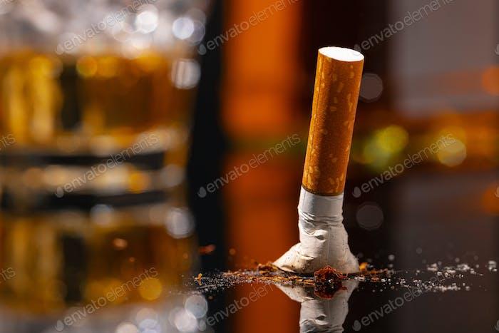 Extinguished cigarette butt on black table close up