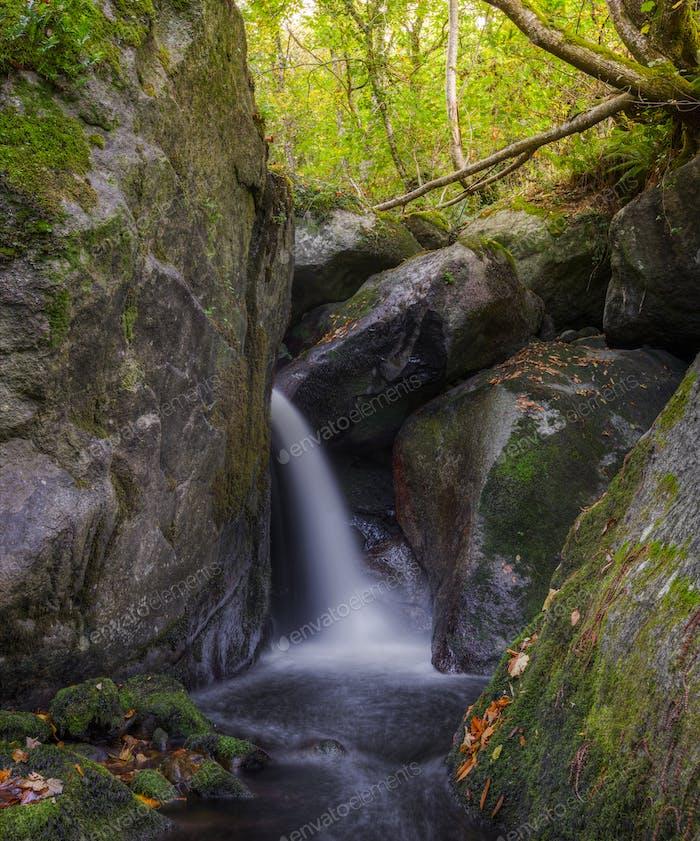 Waterfall jet between huge granite rocks
