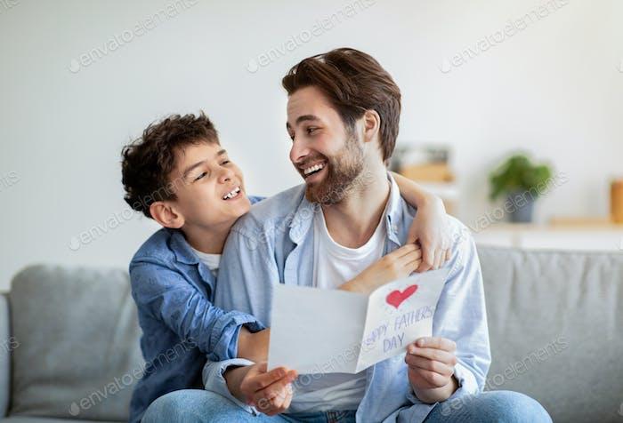 Der glückliche Vatertag. Junge umarmt Papa und gratuliert ihm mit handgemachter Postkarte, lächelnd