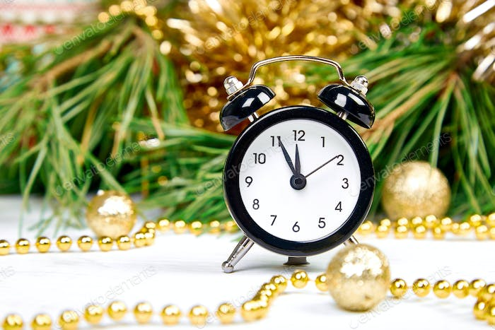 Black Alarm clock and fir tree branch, gold christmas decorations