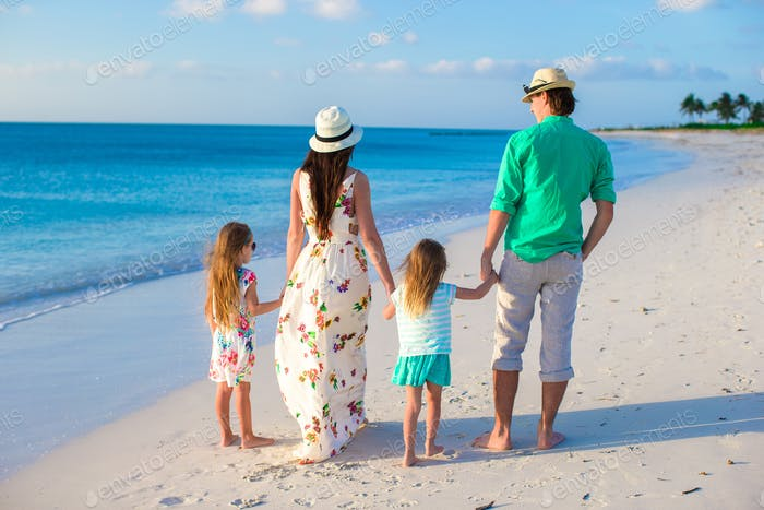 Young family with two kids on tropical vacation in the evening