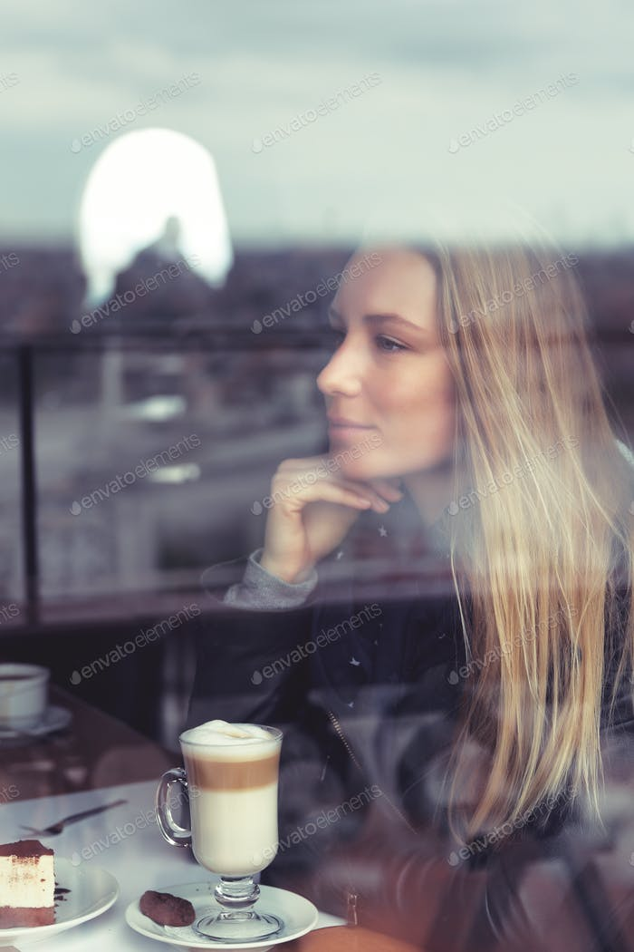 Dreamy girl with latte in cafe