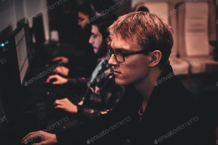 Portrait of young gamer at busy cyberclub
