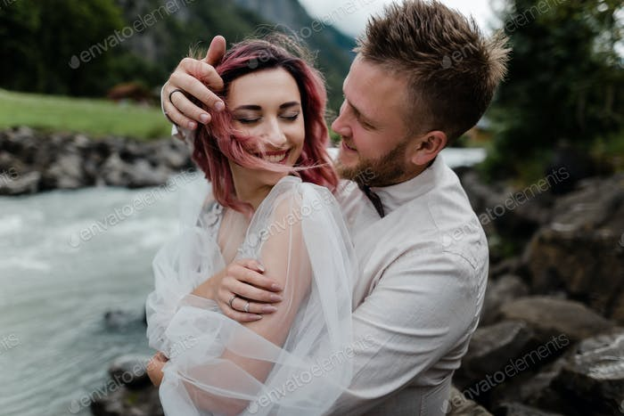 Happy Bride and Groom Hugging While Standing on Bank of Mountain River in Alps