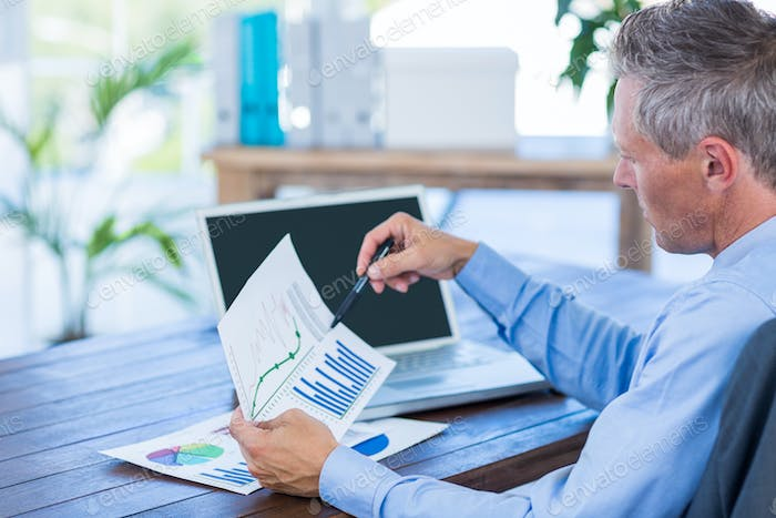 Businessman looking at documents with graphic in office