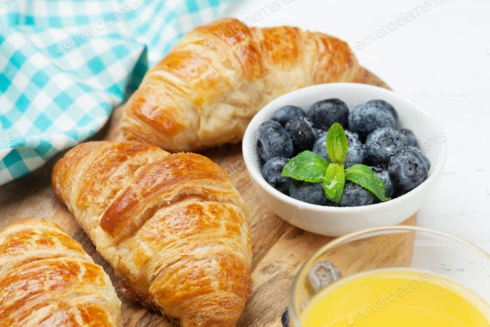 Orange juice and croissants breakfast