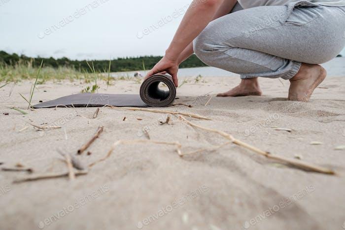 Mann entfaltet eine Yogamatte am Sandstrand in der Nähe des Sees, er macht am Sommertag Übungen im Freien
