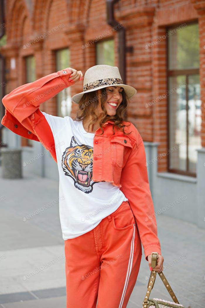 Helle stilvolle Mädchen in einem orangefarbenen Jeansanzug, T-Shirt und Hut geht in der Stadtstraße auf einem