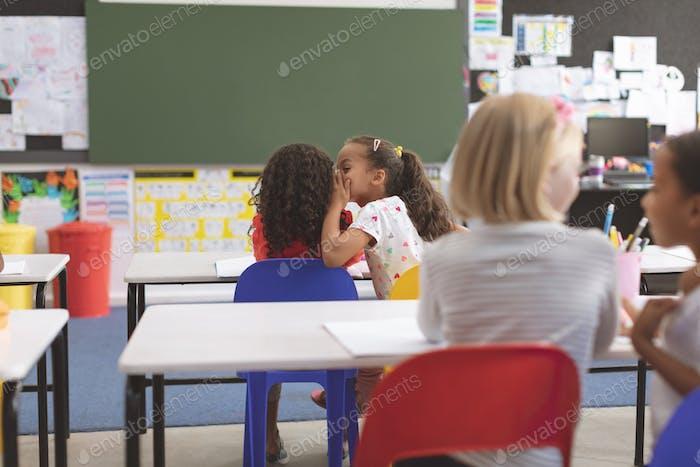 Rückansicht von Schulmädchen flüstert in Ihr Freund Ohr im Klassenzimmer in der Schule
