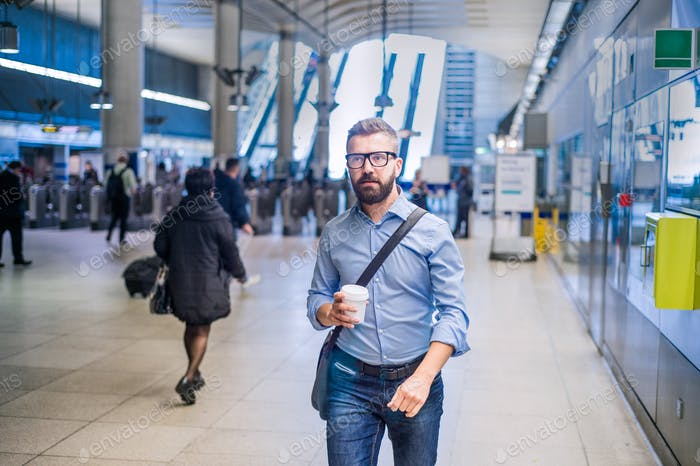 Hipster businessman with coffee cup walking in subway station