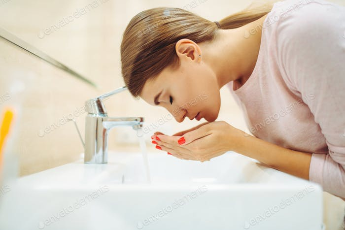 Woman washes her face at the sink in bathroom