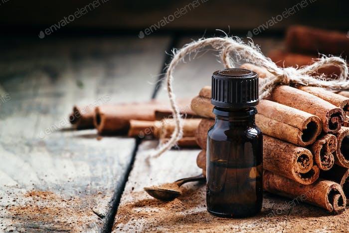 Essentielles Zimtöl in einer kleinen Flasche, gemahlener Zimt und Zimtstangen