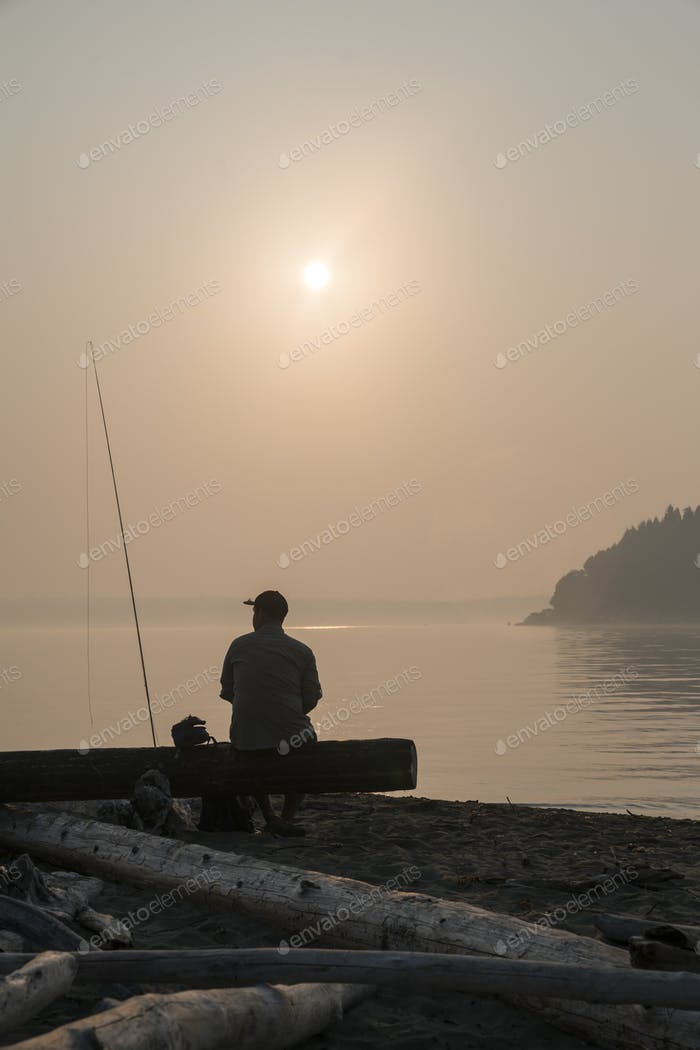 A fly fisherman taking a break from fly fishing on Puget Sound near Port Orchard, Washington USA