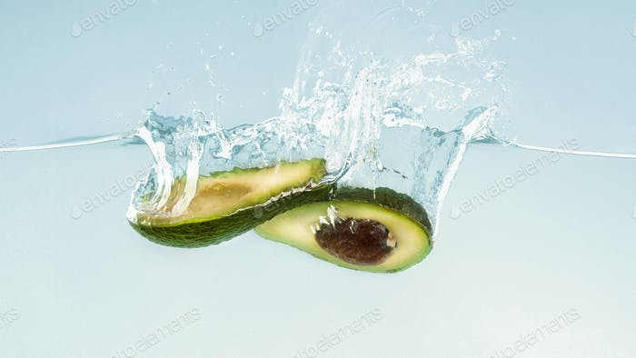 Ripe avocado halves sinking into clear water