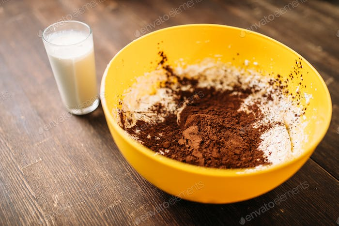 Bowl with dough, chocolate powder, glass of milk