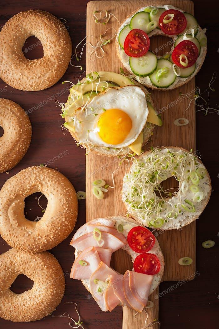 variety of sandwiches on bagels: egg, avocado, ham, tomato, soft