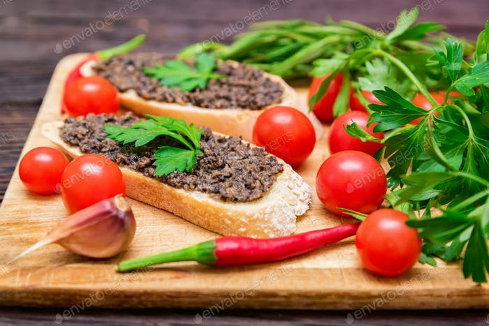 Fresh tasty bruschetta with truffle sauce, chili, parsley and tomates