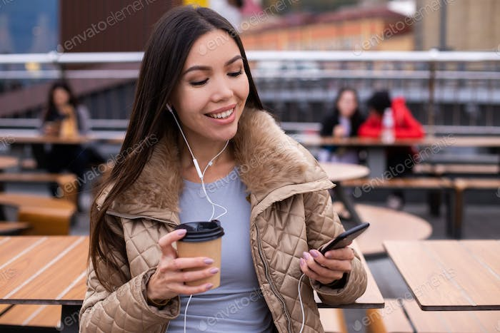 Pretty asian woman in down jacket with coffee joyfully listening music on cellphone outdoor