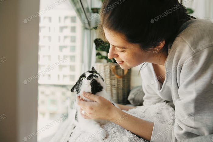 Young woman playing with cute cat