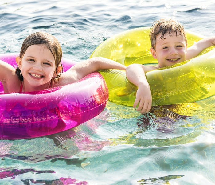 Cheerful brother and sister swimming in the pool