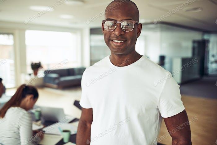 Lächelnd afrikanischen Geschäftsmann mit Kollegen bei der Arbeit im Hintergrund