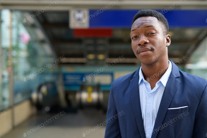 Young handsome African businessman outside the subway train station