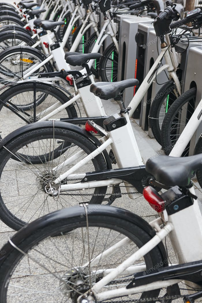 Charging electric bikes in the city. Urban green transportation. Vertical