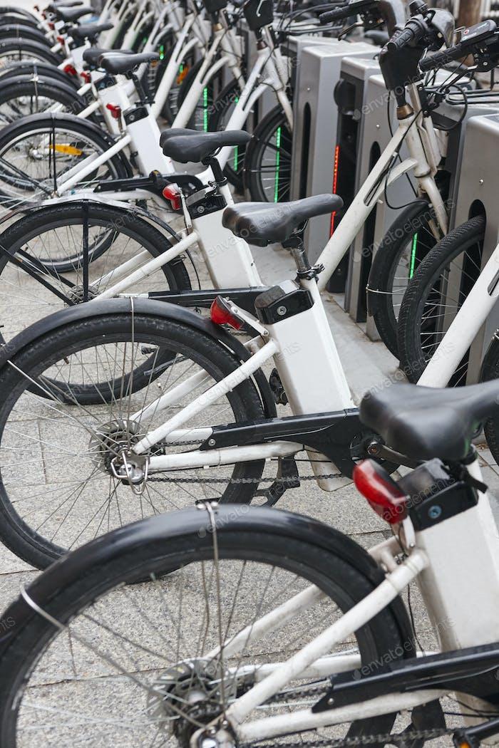 Laden von Elektrofahrrädern in der Stadt. Städtischer umweltfreundlicher Transport. Vertikal