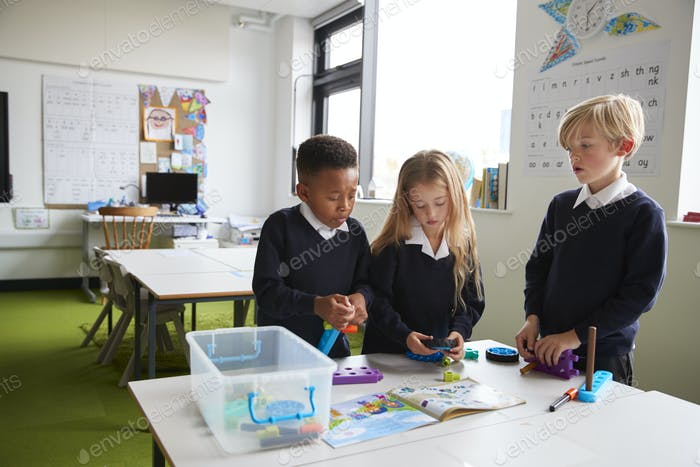 A girl and two boys standing at a table in a primary school classroom working together