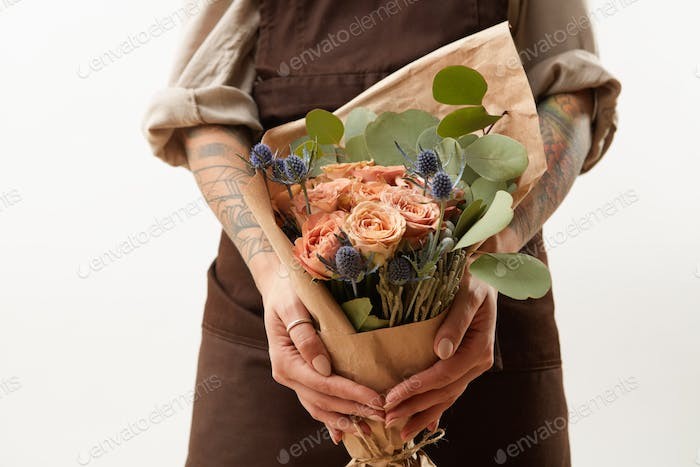 Close-up of greeting bouquet from fresh roses, eryngium and green leaves a in a female's hands