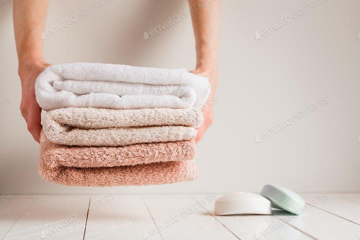 Housewives hands puts towels on the white wooden shelf in the bathroom