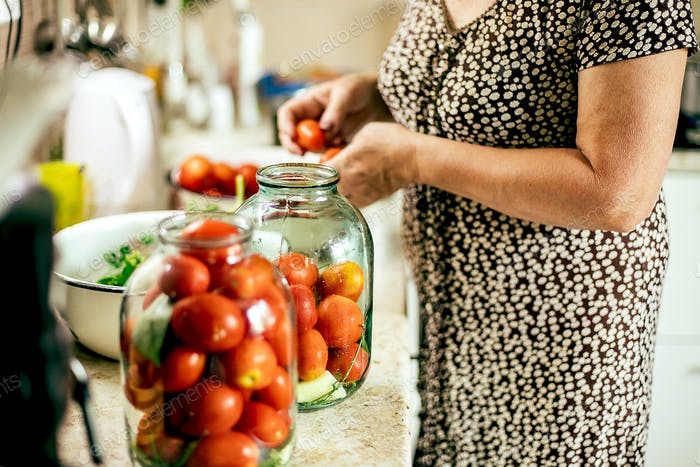 Canning vegetables tomatoes. Woman pickled preserving tomatoes herbs for canning pickling