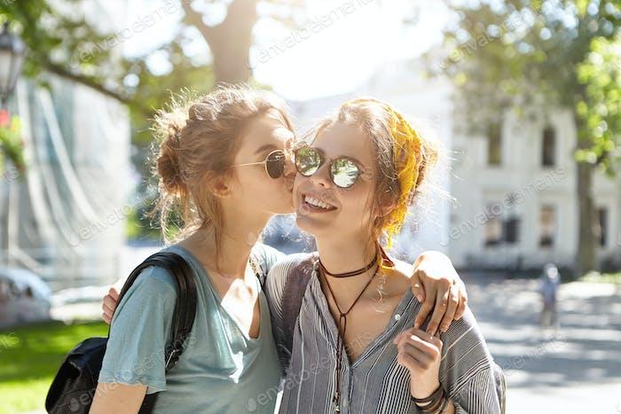 Los mejores amigos se reúnen en el campus mientras van a las clases besándose cariñosamente con