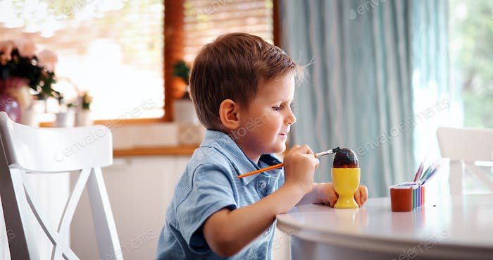 Little kid boy coloring eggs for Easter holiday in domestic kitchen