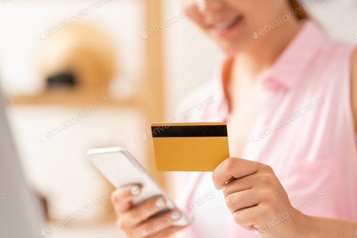Contemporary female shopper entering data from plastic card in smartphone