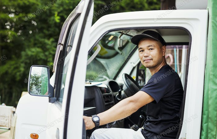 A young man sitting in a truck at a commercial farm in Japan.