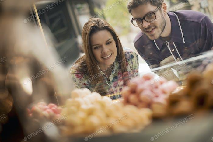 Ein Paar blickt auf das Fenster in einem Süßwarenladen.