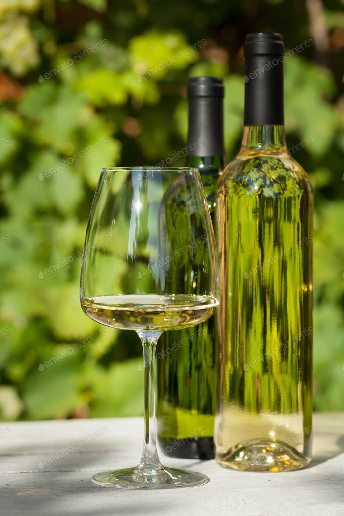 White wine bottles and wineglass