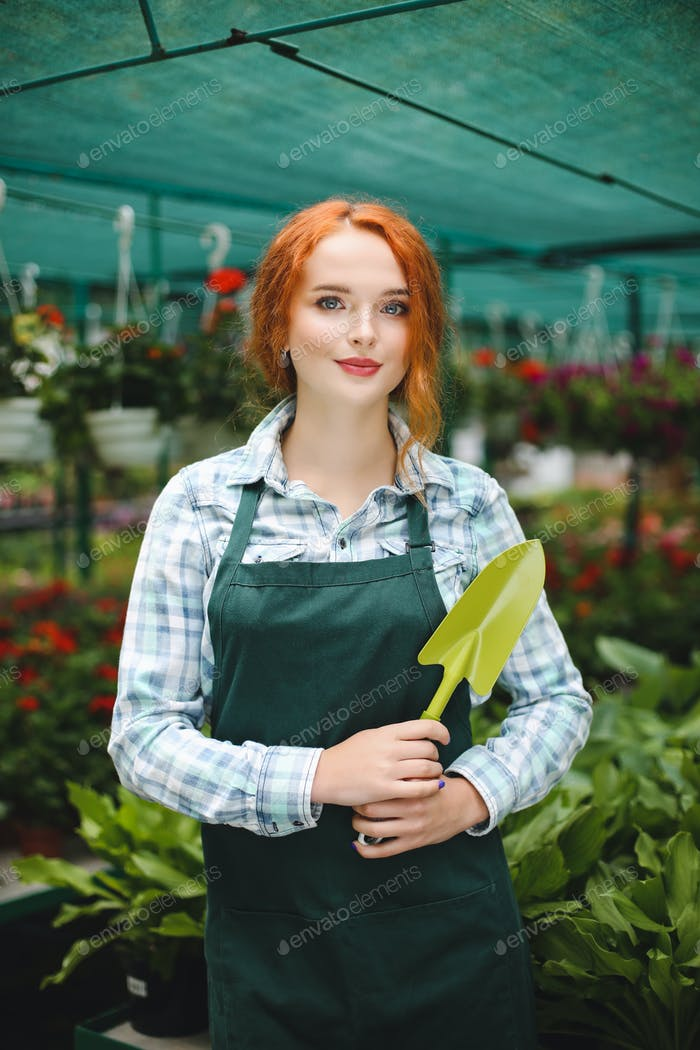 Pretty florist in apron standing with little garden shovel in ha