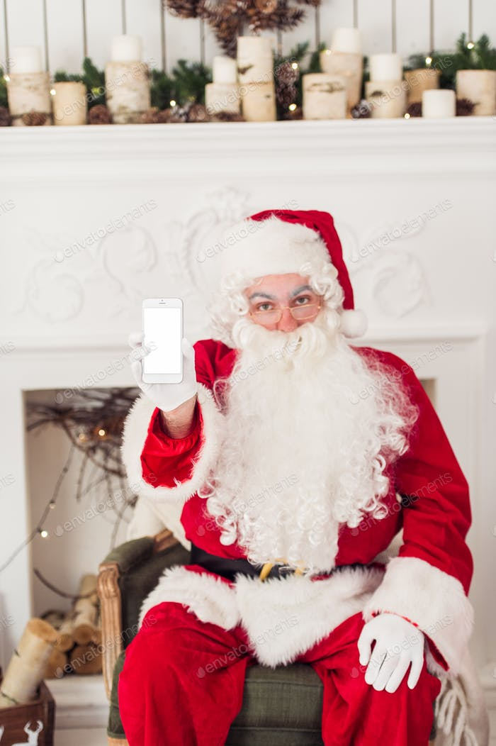 Santa Claus shows a smartphone with fireplace at background