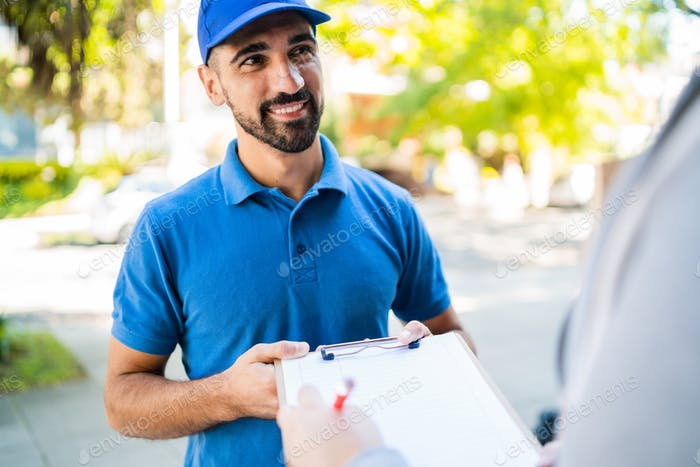 Delivery man carrying package while customer sign in clipboard.