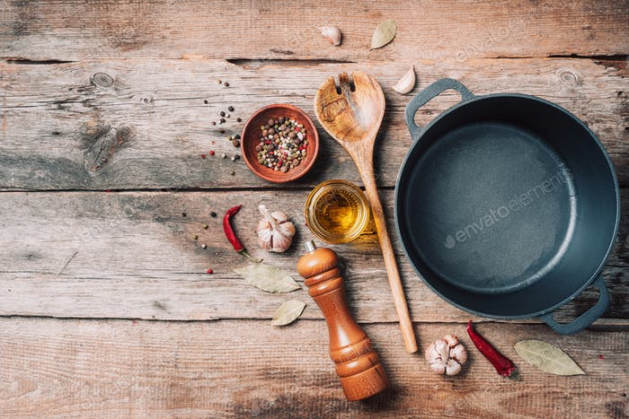 Cast iron pot, spices, pepper shaker, meat fork, oil, spices on wooden background. Top view. Copy