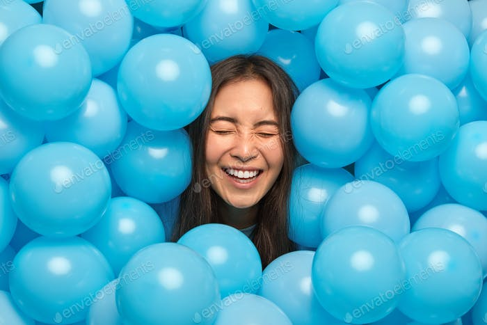 Happy birthday concept. Overjoyed brunette young Asian woman smiles broadly surrounded by inflated h