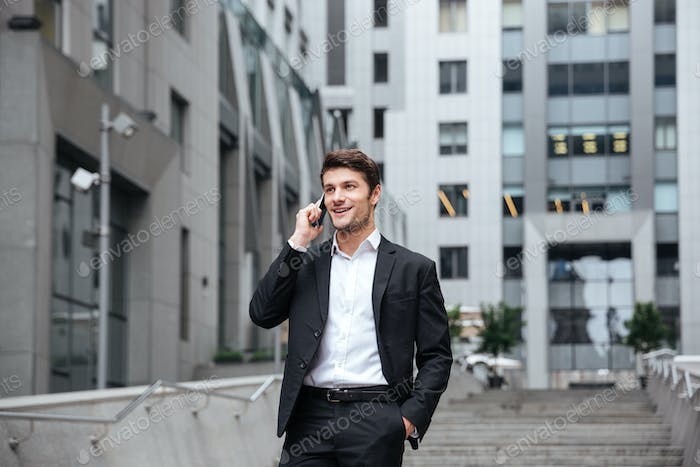 Cheerful young businessman walking and talking on cell phone