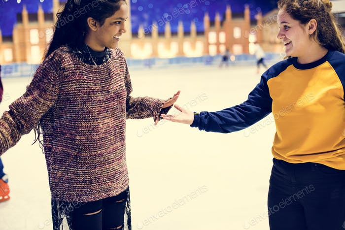 Girl friends playing ice skate together